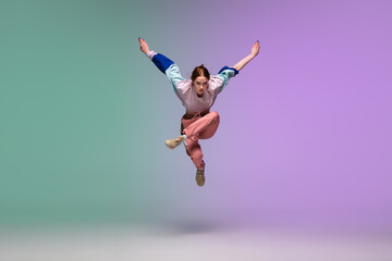 In jump. Beautiful girl dancing hip-hop in stylish clothes on colorful gradient background at dance hall in neon light. Youth culture, movement, style and fashion, action. Fashionable bright portrait.