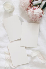 Wedding stationery, still life composition. Greeting cards mockup scene. Blank sheets of paper and pink peony flowers on white linen table cloth. Vintage feminine styled photo, flat lay, top view,
