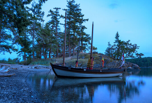 Wooden expedition row boat in a cove at Beaumont Marine Park on South Pender Island, British Columbia.
