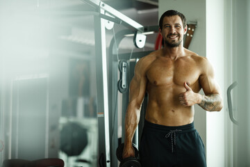 Fitness in gym, sport and healthy lifestyle concept. Handsome athletic man with naked torso making exercises. Bodybuilder male model standing and showing thumb up