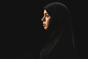 Side view of beautiful muslim woman in hijab isolated on black