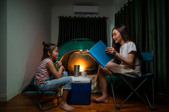 Asian woman reading fairy tale story to her daughter and having fun with camping tent in their bedroom a staycation lifestyle a new normal for social distancing in coronavirus outbreak situation
