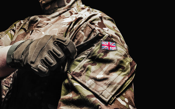 British soldier in camouflage shirt and tactical gloves on black background.