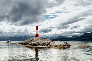 Garden Poster Lighthouse Les Eclaireurs lighthouse on a stone island of the Beagle Channel with catamaran moving away