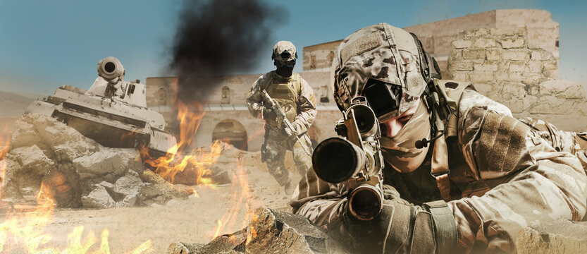 Soldier laying and aiming rifle in desert battlefield with tanks and soldiers attacking.