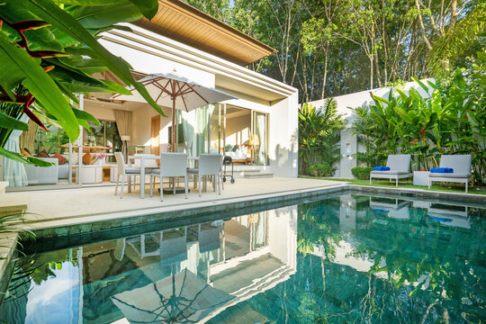 Interior and exterior design of luxury pool villa, house, home feature swimming pool, sunbed, blue beach towels and garden landscape