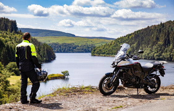 Adventure motorcycle and biker man traveling, standing and watching landscape with lake and mountains, freedom travel lifestyle in Wales UK