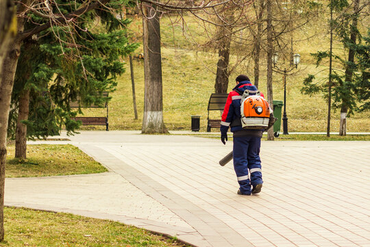 Worker with leaf blower in the park cleans the footway. Processing public spaces.