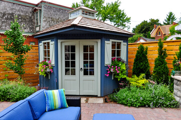 Obraz Wired with electricity and wifi, this large luxury backyard shed makes a perfect garden in the office while working from home.   - fototapety do salonu