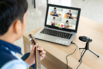 Asian boy playing acoustic guitar virtual happy hour meeting for play music online together with friend in video conference with laptop for a online meeting in video call for social distancing.