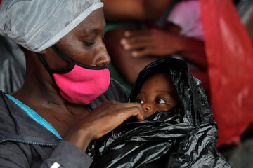 A stranded migrant and her baby shield from the rain after borders were closed due to the coronavirus (COVID-19) pandemic in Tegucigalpa