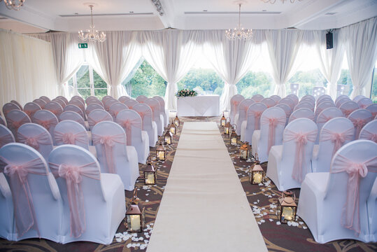Room set up for wedding ceremony with white chairs, camdles and aisle runner