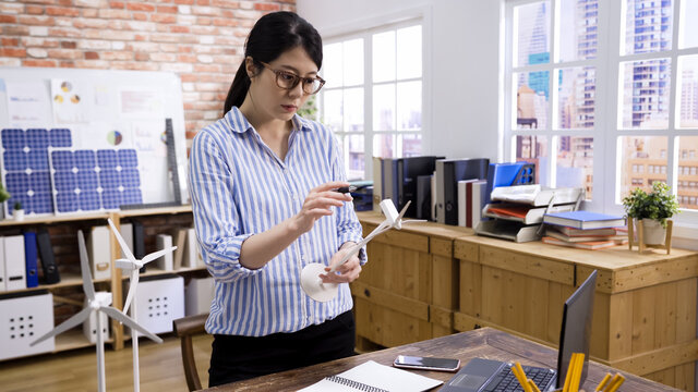 asian korean businesswoman working at desk with model wind turbine making notes. young lady engineer in glasses seriously examining windmill in office. girl employee thinking idea of wind energy.
