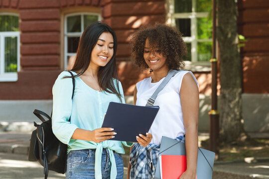 Two multicultural female students standing outdoors near university campus with workbooks