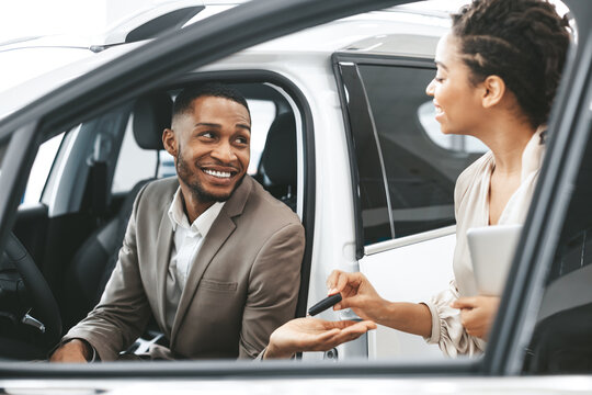 Businessman Taking Key From Dealer For Test Drive In Dealership