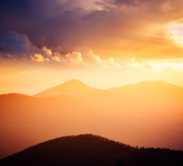 Wall Mural - Evening mountains landscape are illuminated by the sunset. Picture of colorful cloudy sky.