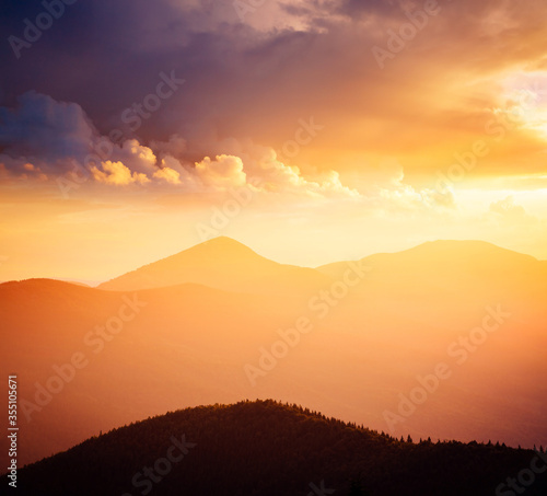 Wall mural Evening mountains landscape are illuminated by the sunset. Picture of colorful cloudy sky.
