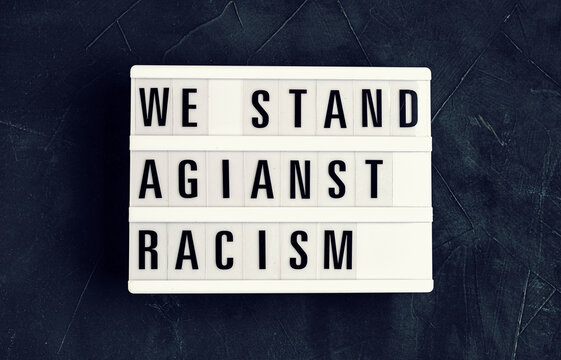 We stand against racism  text on light box on dark background