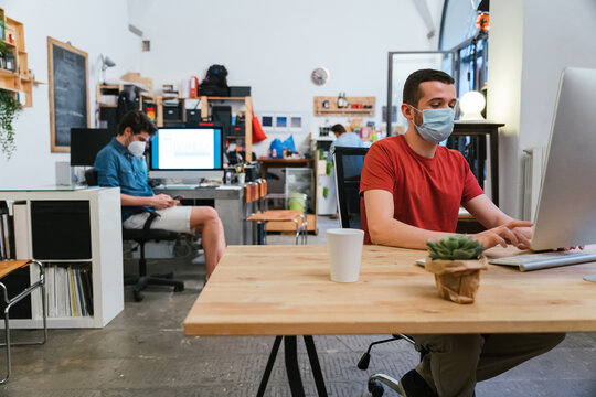 Millennials men with surgical mask at working at computer in office at distance for protection and prevention from Coronavirus, Covid-19