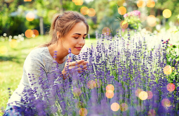 gardening and people concept - happy young woman smelling lavender flowers at summer garden over...