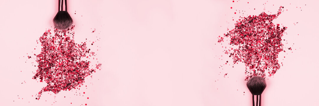 Banner with professional cosmetic makeup brushes with explosion of shiny pink colorful sparkles on pastel pink background with copyspace for your text. Creative make-up concept