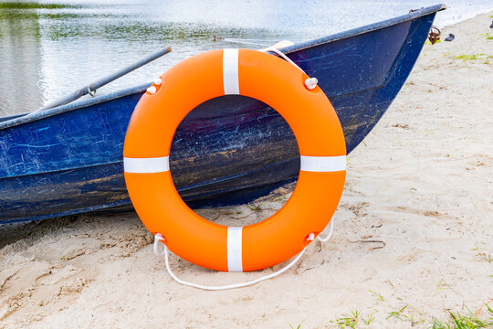 Life buoy hanging on board the boat. The boat stands on the banks of the river. Water safety concept.