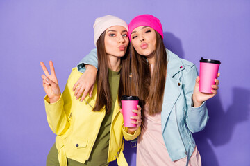 Fototapete - Portrait of nice attractive cheerful girls drinking latte having fun showing v-sign sending air kiss shadow isolated on bright vivid shine vibrant violet lilac purple color background