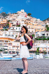 A girl in a sunglasses and a hat stands on the beach in Positano. View of houses and hotels in the background. answers the phone call. Communication and mobile internet network concept.