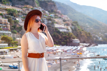 A girl in a sunglasses and a hat stands on the beach in Positano. View of houses and hotels in the background. answers the phone call. Communication and mobile internet network concept. Copy space