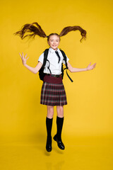Full length photo of little funny crazy little lady schoolgirl pupil jump in uniform with backpack on vibrant yellow background, back to school, learning education concept