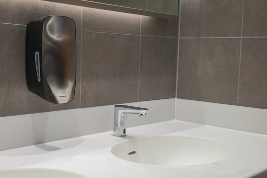 Modern wash hand basin with automatic, hands free tap and soap dispenser. Solid surface worktop and grey tiled wall.