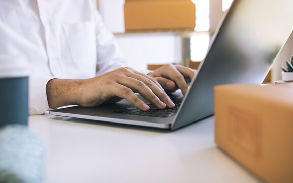 Entrepreneurs are working on taking orders of customers products by typing information tpying keyboard laptop computer in office room.