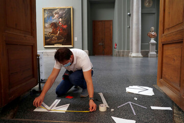 A museum worker installs social distance markers as the Prado museum prepares for reopening on June 6th amid the coronavirus disease (COVID-19) outbreak, in Madrid