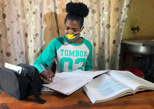 Learner Phuti Ngoetjana tries to study math at her family's one-room brick home during COVID19 outbreak in Tembisa