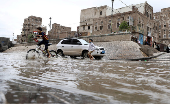 A boy rides a bike in flooded waters after rains in the old quarter of Sanaa,