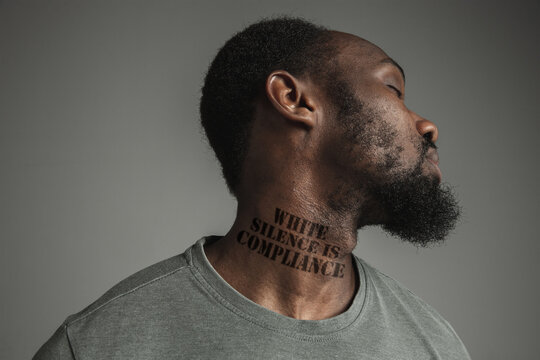 Close up black man tired of racial discrimination has tattooed slogan white silence is compliance on his neck. Concept of human rights, equality, justice, problem of violence and racism. Eyes closed.