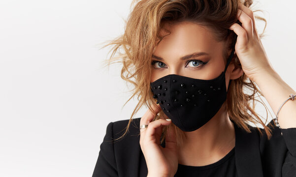 Woman in trendy fashionable outfit during quarantine of coronavirus outbreak. Model dressed stylish black protective face mask on white background