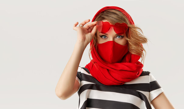 Woman in trendy fashion outfit during quarantine of coronavirus outbreak. Model in protective stylish red face mask and heart shape sunglasses on white background