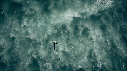 surfer paddling in rough seas