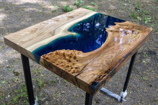 Beautiful wooden table made of elm slab with epoxy resin filling