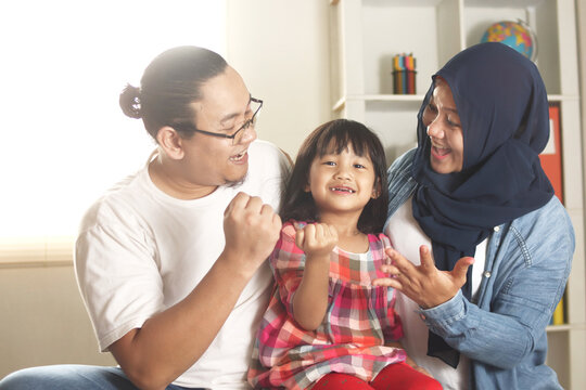Muslim parents and little babgy girl, father and mother with their daughter, happy smiling plays together