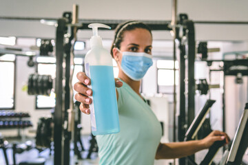 Young brunette woman offers a sanitizer gel to clean our hands at the gym. She's wearing a mask.