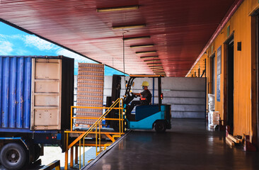 Obraz Forklift stuffing-unstuffing pallets of cargo to container on warehouse leveler dock. - fototapety do salonu