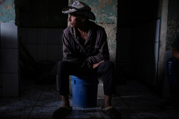 Braulio Rodriguez, 66, who is in charge of keeping the bathroom clean, sits on a bucket in front of open door toilets at the Centro Penal de La Esperanza (La Esperanza Prison)