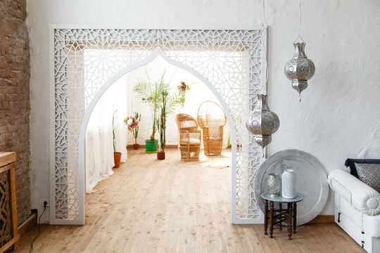 Eastern traditional interior. Arch with beautiful carving. White and gray room