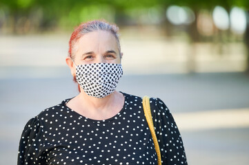 Mature woman with face mask outdoors