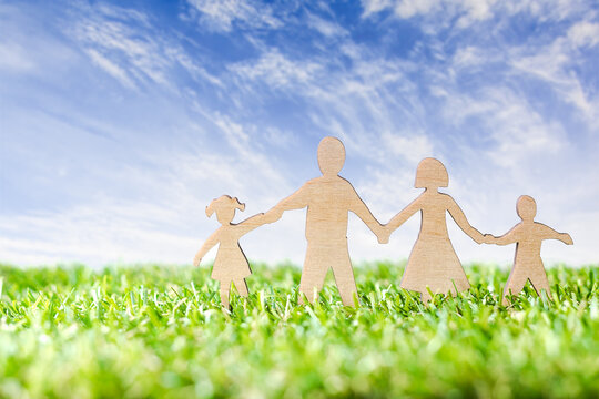 Wood Family Shaped on green grass over beautiful sky.  Green Family Concept.