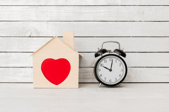 Wood Home Shaped with red heart and alarm clock on white wood over white wood background.