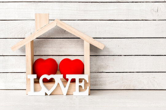 Wood Home Shaped with red heart and love alphabet shaped on white wood over white wood background.