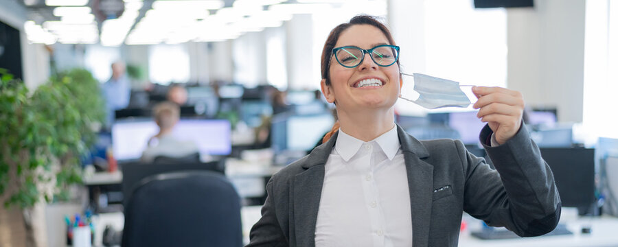 Business woman takes off the mask in the office at the end of quarantine. Coronavirus over time to return to work. The girl breathes freely and smiles. Victory over the pandemic. Return to normal.
